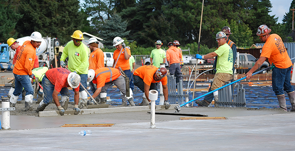 workers smoothing poured concrete