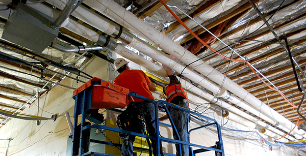 Crews work on ceiling wiring