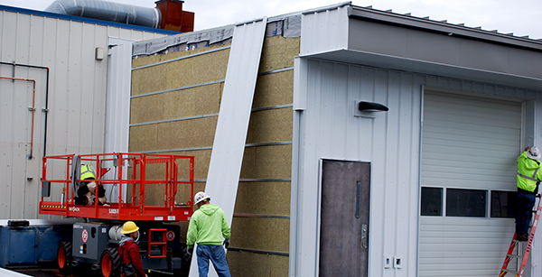 installing external siding to auto shop expansion