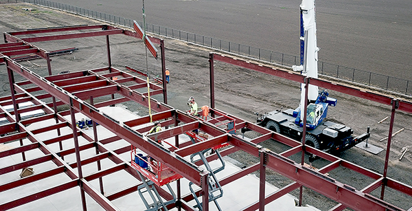crew members place steel truss into position