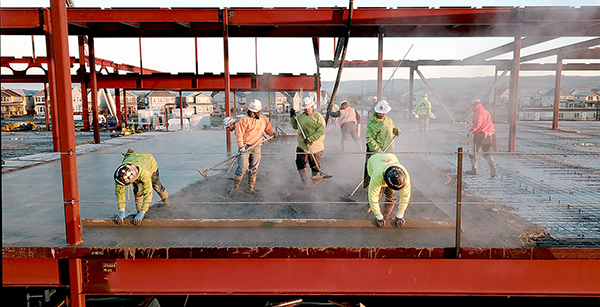 crew members smooth out freshly-poured concrete
