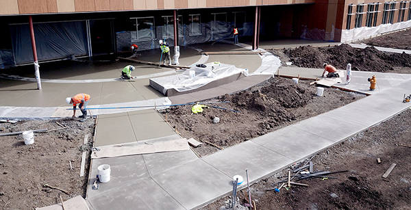 smoothing out fresh concrete on plaza