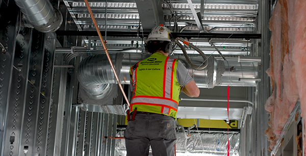 crew member works on overhead conduit